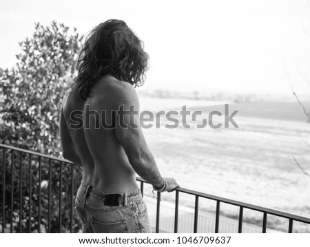 Man with long hair on a roof showing his back #1046709637