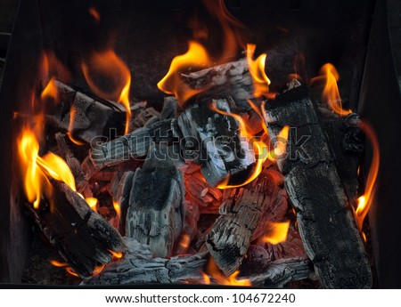 Closeup of charcoal burning under a barbecue grill