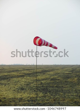Wind sock in the field, red and white color #1046748997