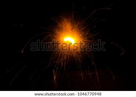 A burning sparkler on a black background #1046770948