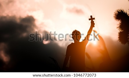 Young man holding and lift cross with light sunset background. christian concept.