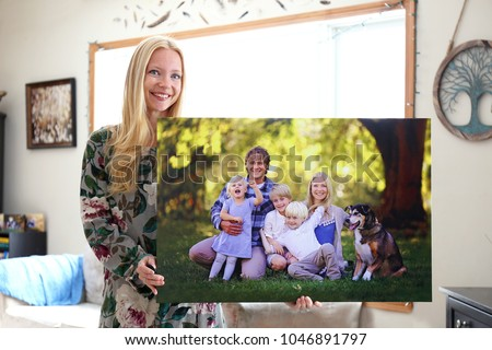 A happy young blonde woman is holding a large wall canvas portrait of her family with young children and a pet dog. #1046891797