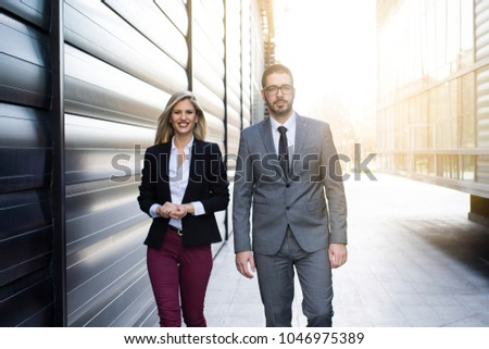 Businessman and businesswoman discussing work while walking #1046975389