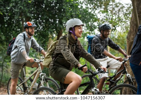 Group of friends ride mountain bike in the forest together #1047156307