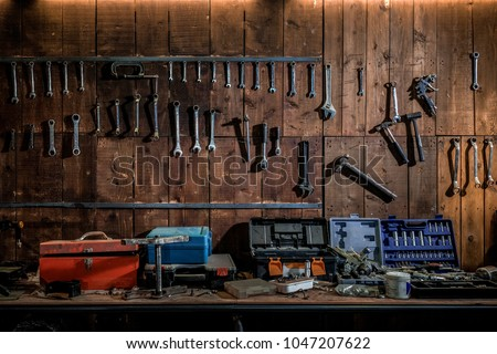 Workshop scene. Old tools hanging on wall in workshop, Tool shelf against a table and wall, vintage garage style  #1047207622