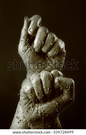 Monochrome image of two muddy fists
