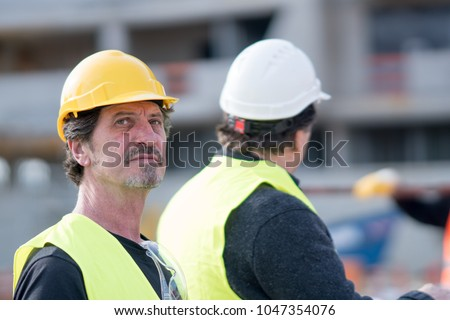 Absorbed and pensive construction worker wearing yellow reflective vest and hardhat looking away #1047354076