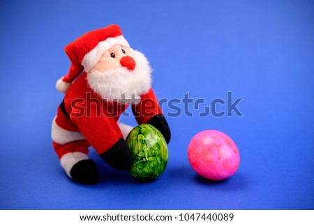little santa claus with green and pink easter egg on blue ground #1047440089
