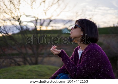 Beautiful female smoking weed in nature #1047442153
