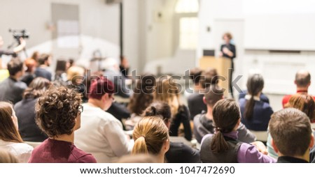 Female speaker giving presentation in lecture hall at university workshop. Audience in conference hall. Rear view of unrecognized participant in audience. Scientific conference event. #1047472690