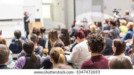 Female speaker giving presentation in lecture hall at university workshop. Audience in conference hall. Rear view of unrecognized participant in audience. Scientific conference event. #1047472693