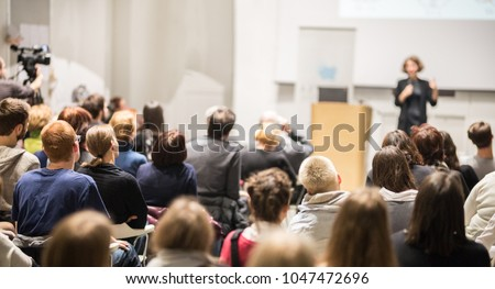 Female speaker giving presentation in lecture hall at university workshop. Audience in conference hall. Rear view of unrecognized participant in audience. Scientific conference event. #1047472696