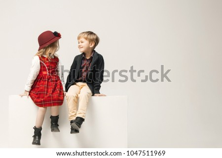 Cute stylish children on white studio background. Two beautiful teen girl and boy sittting together. Stylish young teen girl posing at studio. Sublings day. Teen and kids fashion concept.  #1047511969