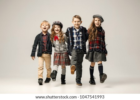 The group of happy smiling teen girls and boys. Sublings day. Stylish young teen girls posing at studio. Classic autumn style. Teen and kids fashion concept. children's fasion concept #1047541993