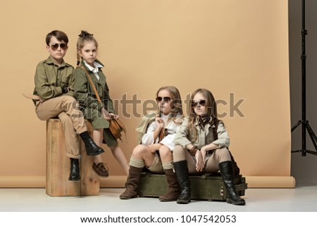 The group of beautiful teen girls and boys on a pastel studio background. Stylish young teen girls posing at studio. Safari style. Classic style. Teen and kids fashion concept. children's fasion