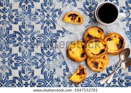 Egg tart, traditional Portuguese dessert, pastel de nata on a parchment paper. Blue textile background. Top view. Copy space. #1047552781