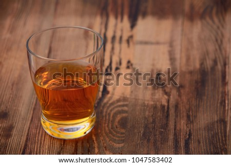 a glass of Scotch or whiskey on a wooden texture background #1047583402