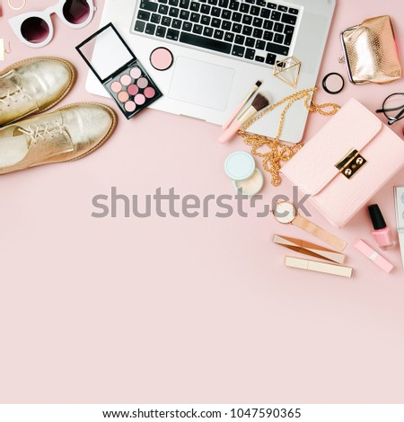 Fashion blogger workspace with laptop and female accessory, cosmetics products on pale pink table. flat lay, top view
