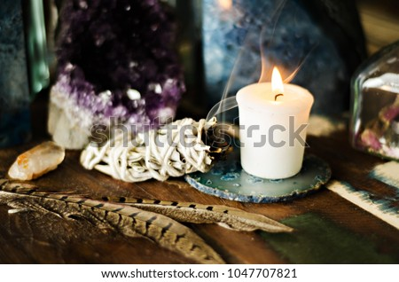 sacred space still life with amethyst candle feathers and sage