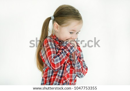 Portrait of an embarrassed and shy beautiful little girl in a checkered shirt looking modestly in the floor covering her mouth with her hands isolated against a white background in the studio #1047753355