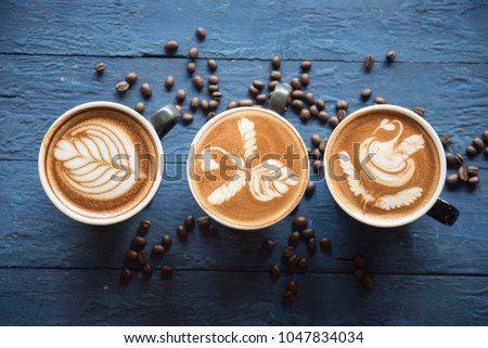 cups of cappuccino with latte art on blue wooden background,top view,flat lay #1047834034