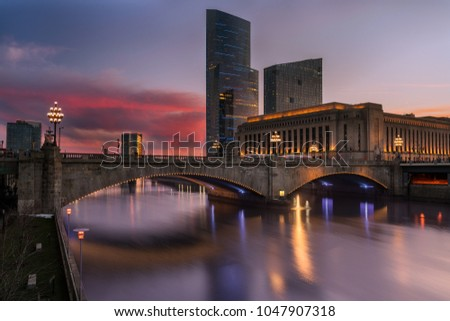 Sunset behind a cluster of buildings that symbolize both old and new - the art-deco monolith that is the Post Office, against the backdrop of the modern high-rises made of steel and glass.