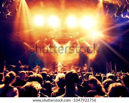 Concert crowd clapping a band performance inside a venue #1047922756