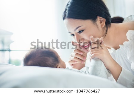 Mother hands holding newborn baby feet. Close up portrait of beautiful young asian mother with her newborn baby. Healthcare and medical love lifestyle mother's day concept #1047966427