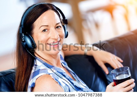 Happy smiling woman relaxing and listening to music #1047987388