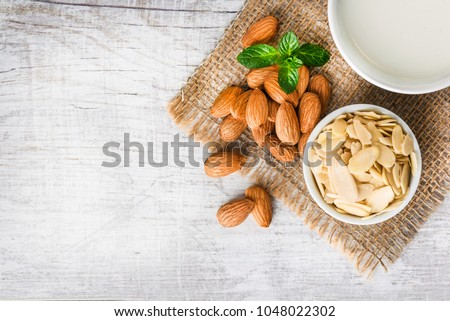 Almonds nuts and peeled almond on white table on jut. Almonds with milk in cup. Top view of almonds nuts. #1048022302