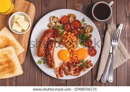 Traditional full English breakfast with fried eggs, sausages, beans, mushrooms, grilled tomatoes and bacon on wooden background. Top view #1048036531
