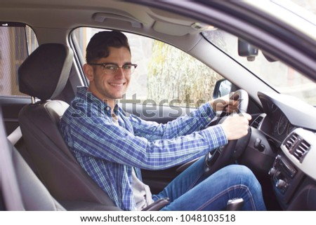young adult driving the car #1048103518