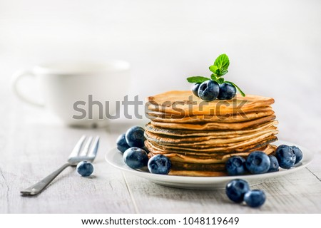 Pancakes with blueberries and mint leaf on top. Pile of small homemade pancakes with forest fruits. Heap of flat thin cake in background. #1048119649