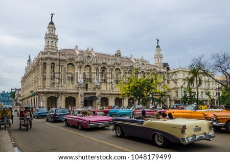 HAVANA, CUBA - JUNE 9, 2016: Colorful classic convertible cars are popular with tourists as they are driven in the La Habana Vieja neighborhood with the Gran Teatro in front of them. #1048179499