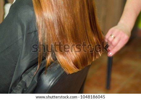 Long red woman hair during haircut in beauty hairdresser salon.  #1048186045