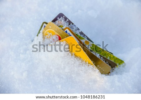 Frozen Bank Account Concept photo. Credit Cards buried in snow.