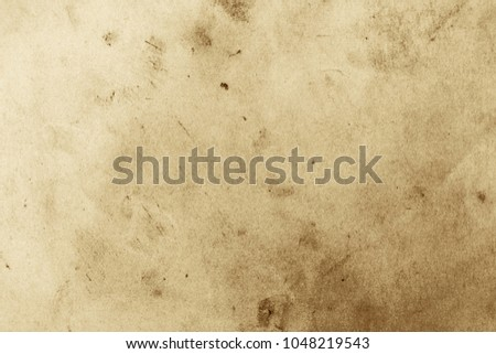 Blank aged paper sheet as old dirty frame background with dust and stains. Front view. Vintage and antique art concept. Detailed closeup studio shot. Toned #1048219543