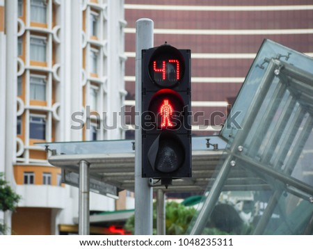 Pedestrian traffic light with countdown timer with a background of modern buildings in urban area. Macau, China. #1048235311