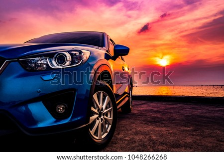 Blue compact SUV car with sport and modern design parked on concrete road by the sea at sunset. Environmentally friendly technology. Business success concept. #1048266268