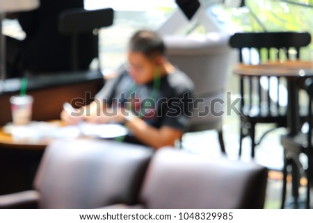 Blurry focus of a man sitting while reading at coffee in urban life style concept  #1048329985