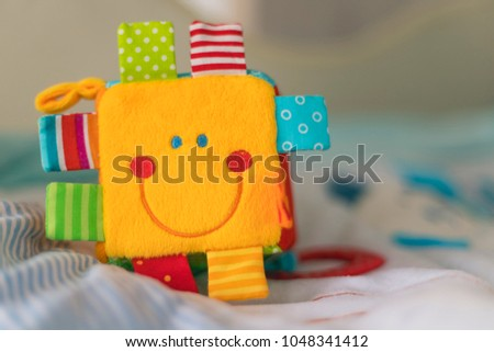 colorful plush cube with a laughing face #1048341412