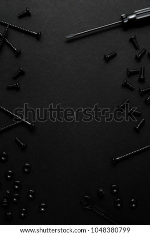 Creative concept photo of painted tools and nails on black background. #1048380799