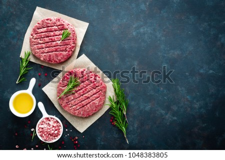 Fresh minced beef meat burgers with spices on dark background. Raw ground beef meat. Flat lay. Top view #1048383805