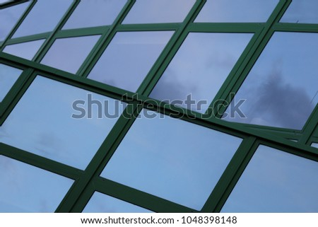 Outdoor view of a modern wall made of polygonal glass windows. Pattern of reflective flat surfaces and green lines. Modern design. New building facade. Geometric image. Abstract architectural picture.
