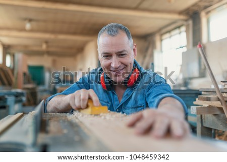 Man doing woodwork in carpentry. Carpenter work on wood plank in workshop. Smiling woodworker. Attractive man doing woodwork in carpentry. Profession, carpentry, woodwork and people concept  #1048459342
