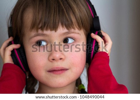 Picture of happy pretty child little girl with big headphones at home. Joyful child girl listening to music on gray blurred background. Home, technology and music concept.