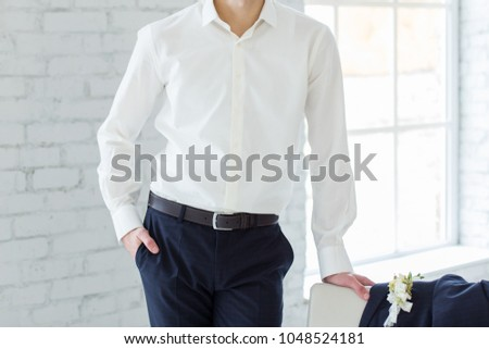 the groom puts on a suit in the room #1048524181