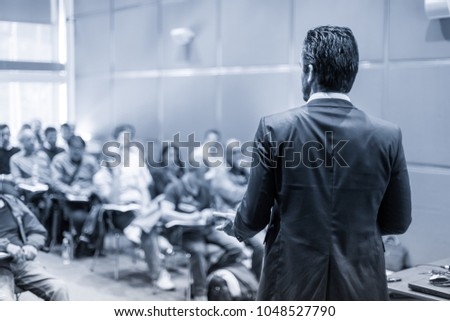 Rear view of speaker giving a talk at business meeting. Audience in the conference hall. Business and Entrepreneurship concept. Black and white blue toned image. #1048527790