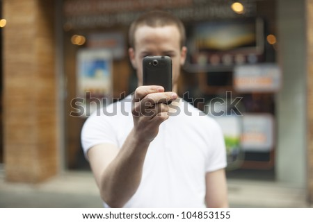 Men on street photographing with smartphone, background is blured city #104853155
