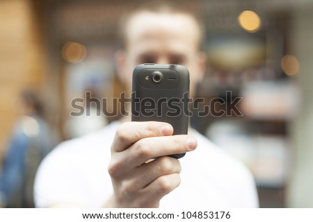 Men on street photographing with mobile phone, background is blured city #104853176